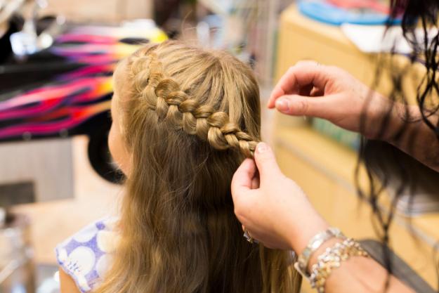 Girl getting hair braid at KidSnips